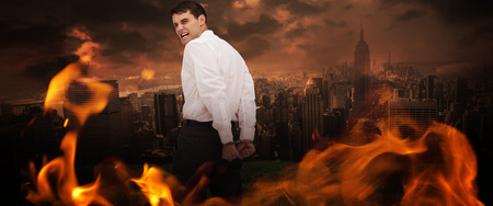 restraining device: Rear view of young businessman wearing handcuffs against stormy sky over city Stock Photo
