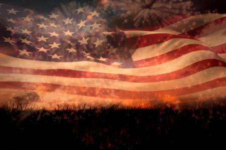 Digitally generated american flag rippling against colourful fireworks exploding on black background Stock Photo