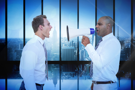 businessman using a megaphone: Businessman yelling with a megaphone at his colleague against room with large window looking on city