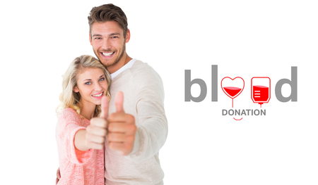 donation: Attractive couple showing thumbs up to camera against blood donation Stock Photo