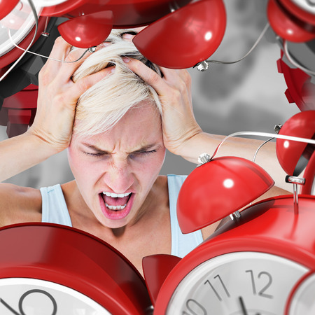 screaming head: Angry blonde woman screaming and holding her head  against grey vignette