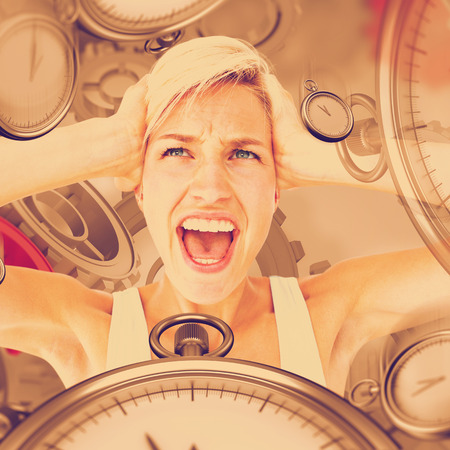 screaming head: Angry blonde screaming and holding her head  against grey vignette Stock Photo