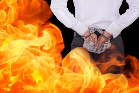 restraining device: Businessman in handcuffs holding bribe against black