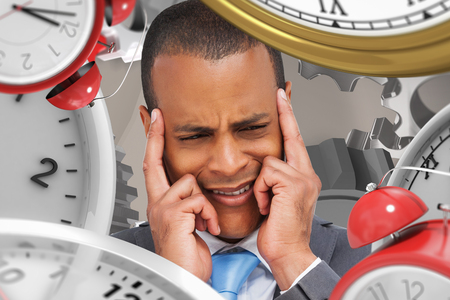 ticking away: Stressed businessman putting his fingers on his temples against grey background with vignette Stock Photo