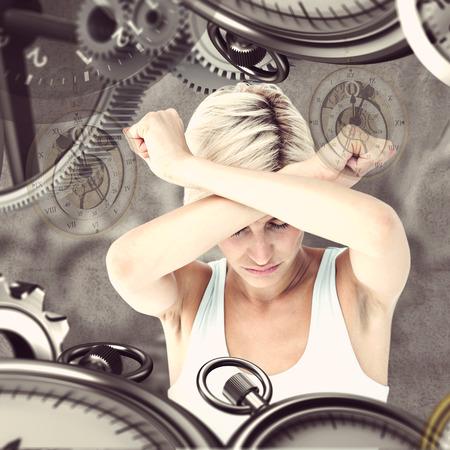 desolaci�n: Malestar mujer sosteniendo sus brazos delante de su cabeza contra el fondo gris Foto de archivo