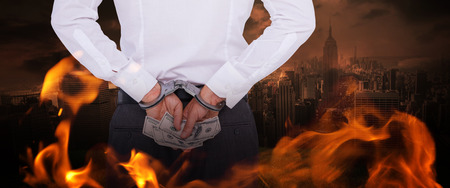 restraining device: Businessman in handcuffs holding bribe against stormy sky over city