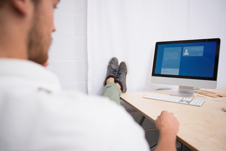 legs crossed: Website interface against businessman with legs crossed at ankle on office desk