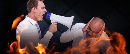 businessman using a megaphone: Businessman yelling with a megaphone at his colleague against dark grey room Stock Photo
