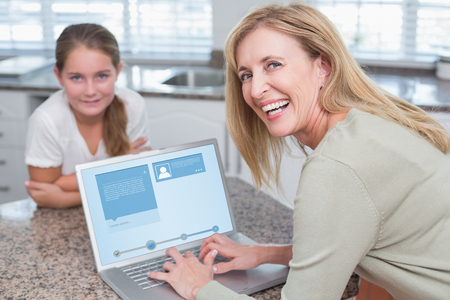 mujeres maduras: Interfaz Web site contra la madre feliz usando la computadora port�til con su hija Foto de archivo