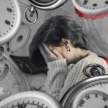 desolaci�n: Chica con la cabeza en las manos contra el fondo gris Foto de archivo