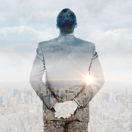 hands behind back: Young businessman standing with hands behind back against clouds over city