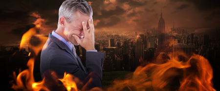 Businessman with headache against stormy sky over city Stock Photo