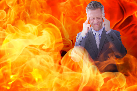 wincing: Businessman with headache against fire Stock Photo