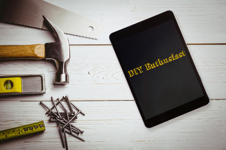 enthusiast: The word diy enthusiast and tablet pc against desk with tools