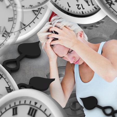 desolaci�n: Mujer rubia triste con dolor de cabeza sosteniendo su cabeza contra el fondo gris Foto de archivo