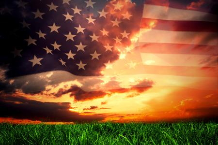 濃い青とオレンジ色の空の下で緑の芝生に対するアメリカ合衆国のフラグ