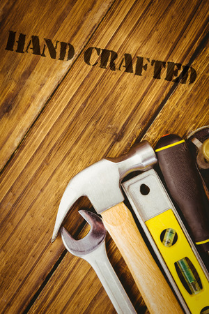 hand crafted: The word hand crafted against desk with tools