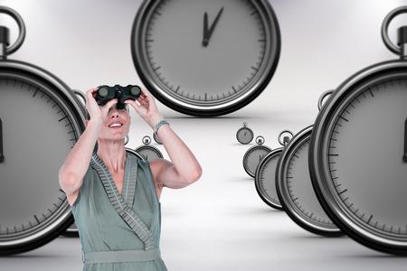 looking through: A businesswoman looking through binoculars against grey background
