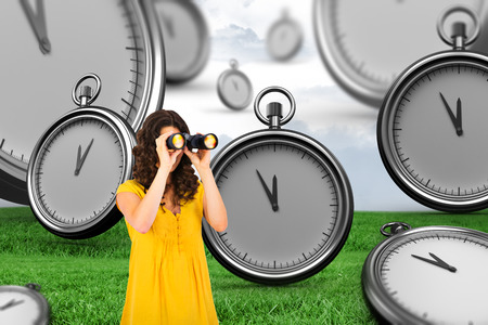 using binoculars: Casual young woman using binoculars against grey sky over field Stock Photo