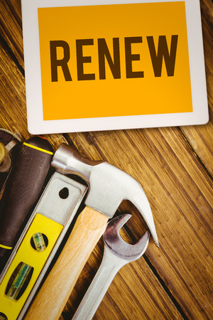 to renew: The word renew and tablet pc against desk with tools