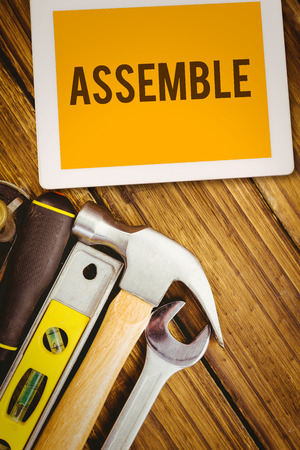assemble: The word assemble and tablet pc against desk with tools Stock Photo
