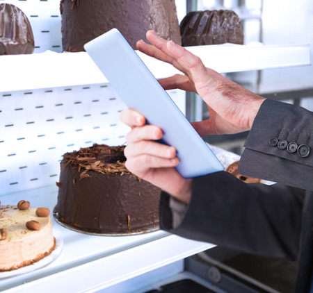 coffee cake: Businessman scrolling on his digital tablet against close up of desert like swiss roll and coffee cake