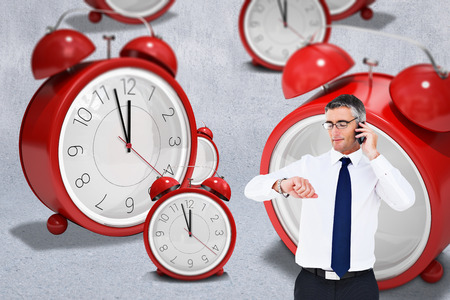 wrist watch: Businessman on the phone looking at his wrist watch against grey wall