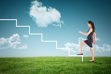 stepping: Businesswoman stepping up against blue sky over green field Stock Photo
