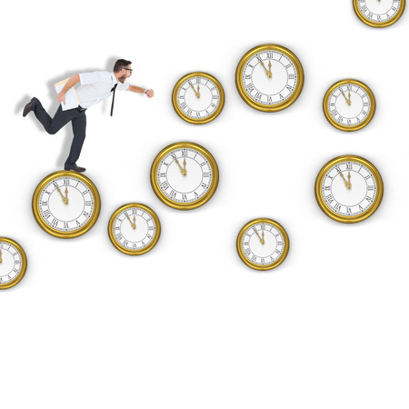 running late: Geeky young businessman running late against clocks Stock Photo