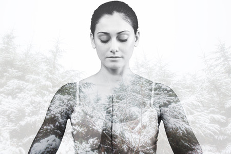 peaceful: Peaceful woman in white sitting in lotus pose against snowy forest Stock Photo