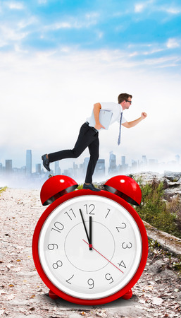 late 20s: Geeky businessman running late against stony path leading to misty cityscape Stock Photo