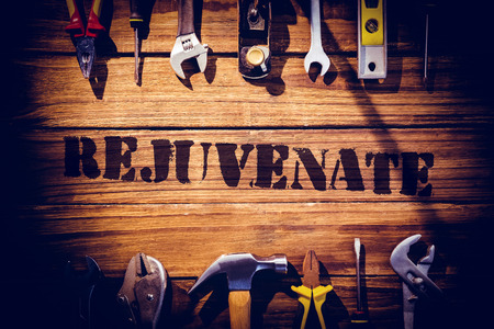 revitalize: The word rejuvenate  against desk with tools Stock Photo