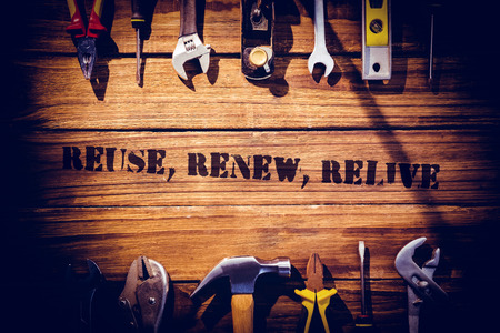 relive: The word reuse, renew, relive against desk with tools Stock Photo