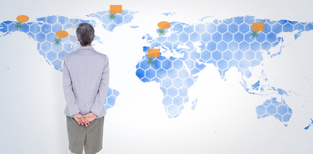 standing against: Businesswoman standing against world map Stock Photo