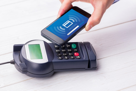 eftpos: Processing screen against man using smartphone to express pay Stock Photo