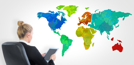 swivel chair: Businesswoman sitting on swivel chair with tablet against colourful world map