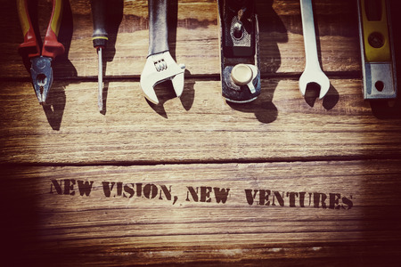ventures: The word new vision, new  ventures against desk with tools