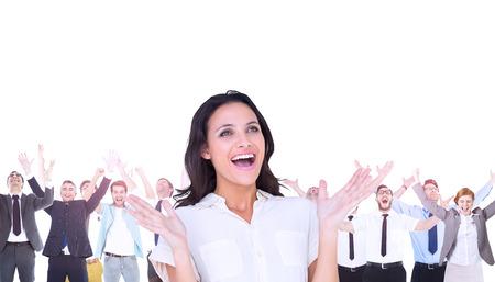 surprised: Imagen compuesta de morena sorprendió con las manos hacia arriba y sonriendo Foto de archivo