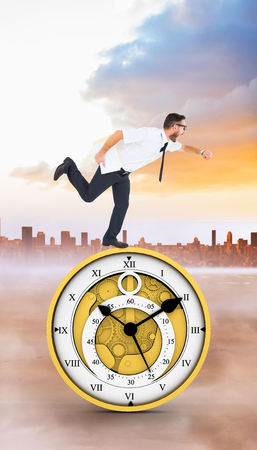 running late: Geeky young businessman running late against city on the horizon Stock Photo