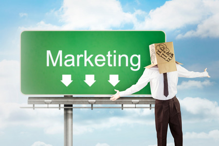 arms out: Anonymous businessman with arms out against signpost showing marketing direction Stock Photo