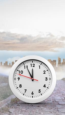 urban sprawl: countdown to midnight on clock against rocky path leading to large urban sprawl Stock Photo