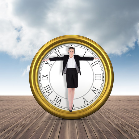 balancing act: Businesswoman performing a balancing act against cloudy sky background