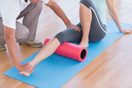 personal trainer: Trainer working with woman on exercise mat in fitness studio