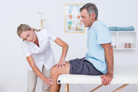 의사는 의료 사무실에서 그녀의 환자 무릎을 검사 스톡 콘텐츠