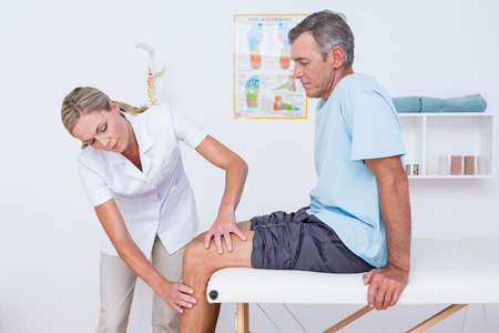 pain: Doctor examining her patient knee in medical office Stock Photo