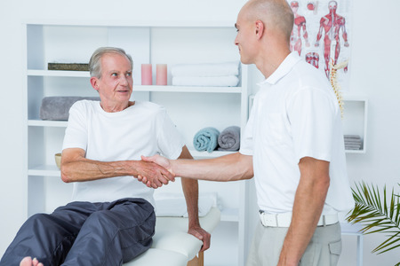 man arm: Patient shaking hands with doctor in medical office Stock Photo