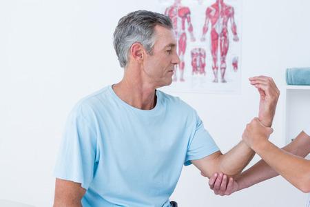 fisioterapia: Doctor que examina el brazo del paciente en el consultorio médico