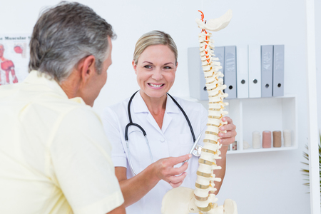 spine: Doctor showing her patient a spine model in medical office