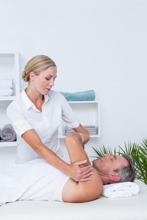 dolor  muscular: Doctor examining her patient arm in medical office Foto de archivo