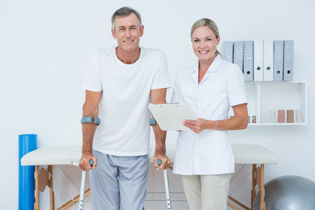 muscle retraining: Doctor and patient with crunch looking at camera in medical office